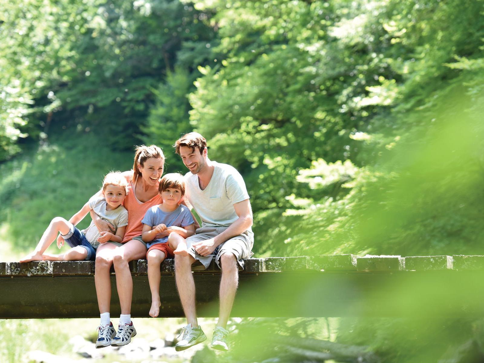 Family Sitting on Bridge