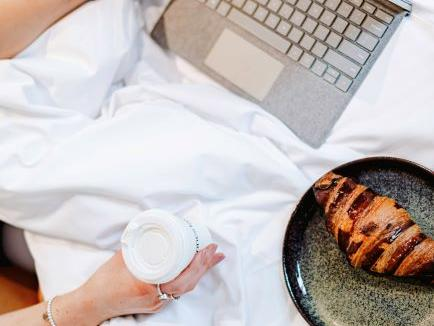 Coffee croissant laptop in bed