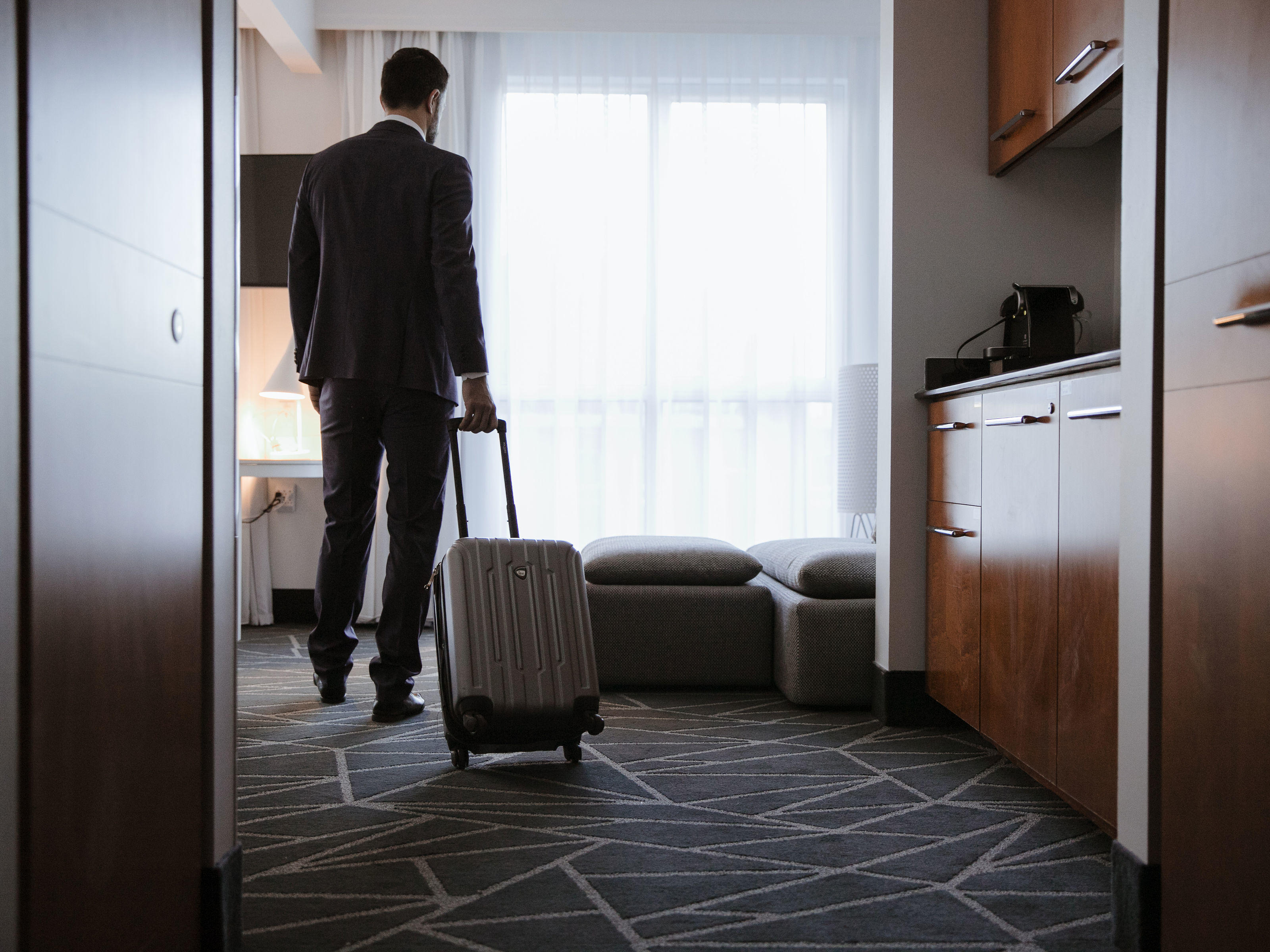 Business Traveler wheeling suitcase into suite
