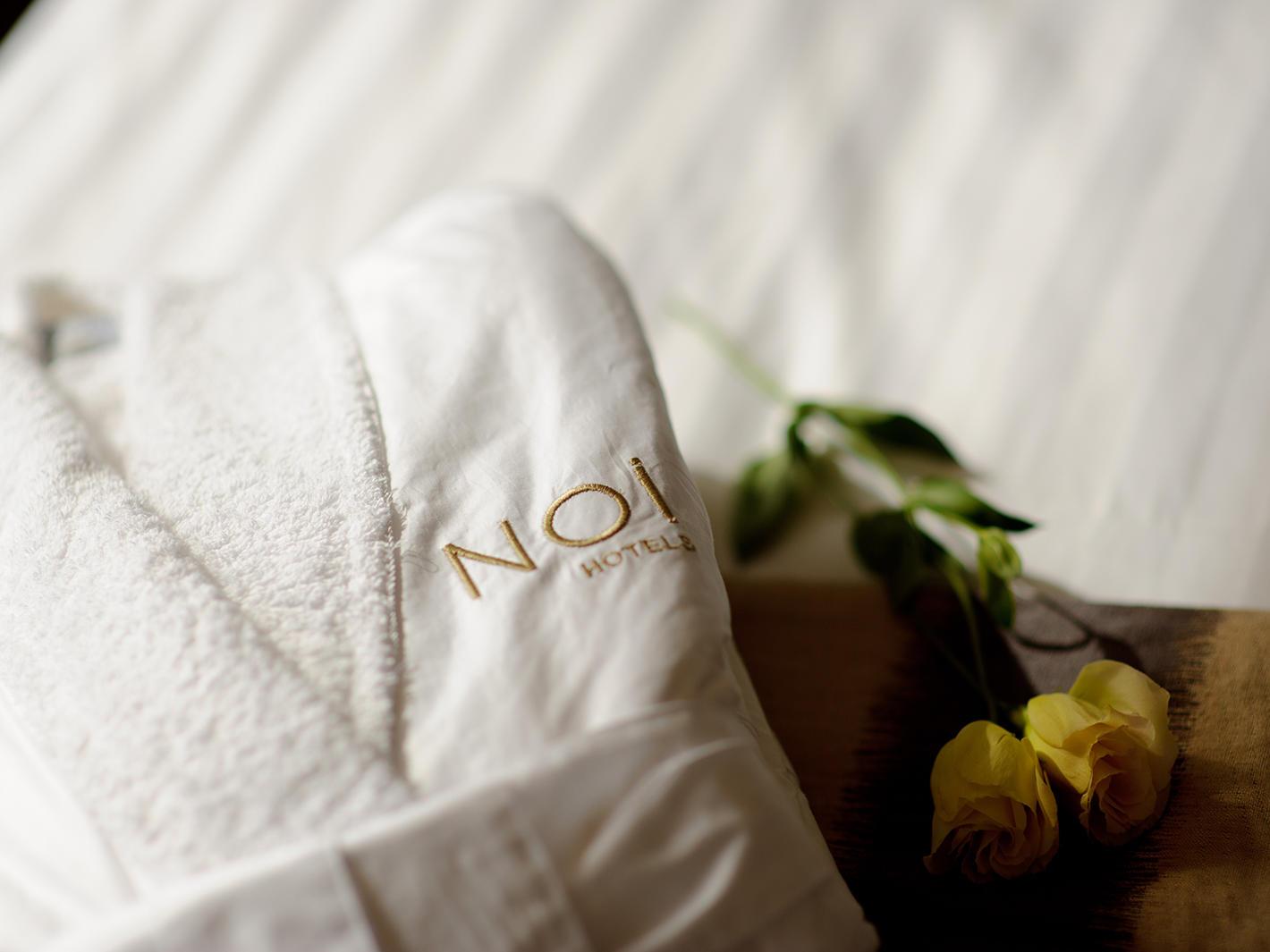 white bathrobe & 2 yellow roses at NOI Vitacura hotel