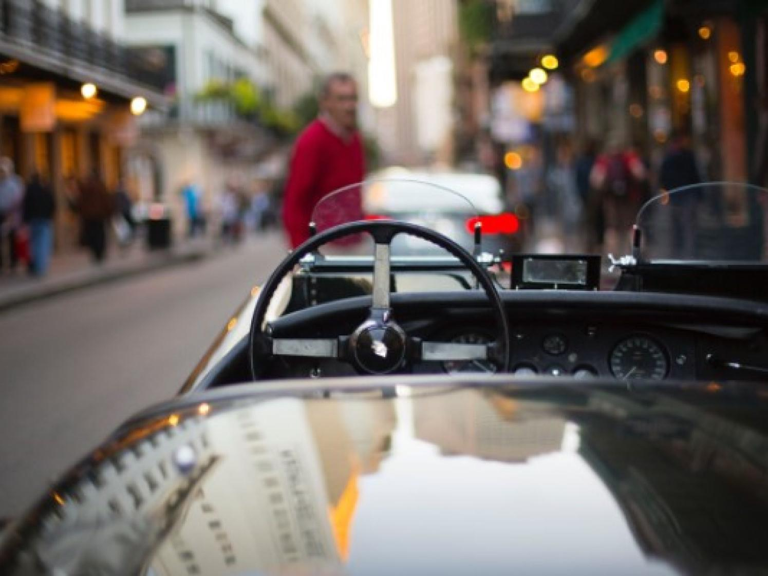 A closeup picture of a convertible car in the streets