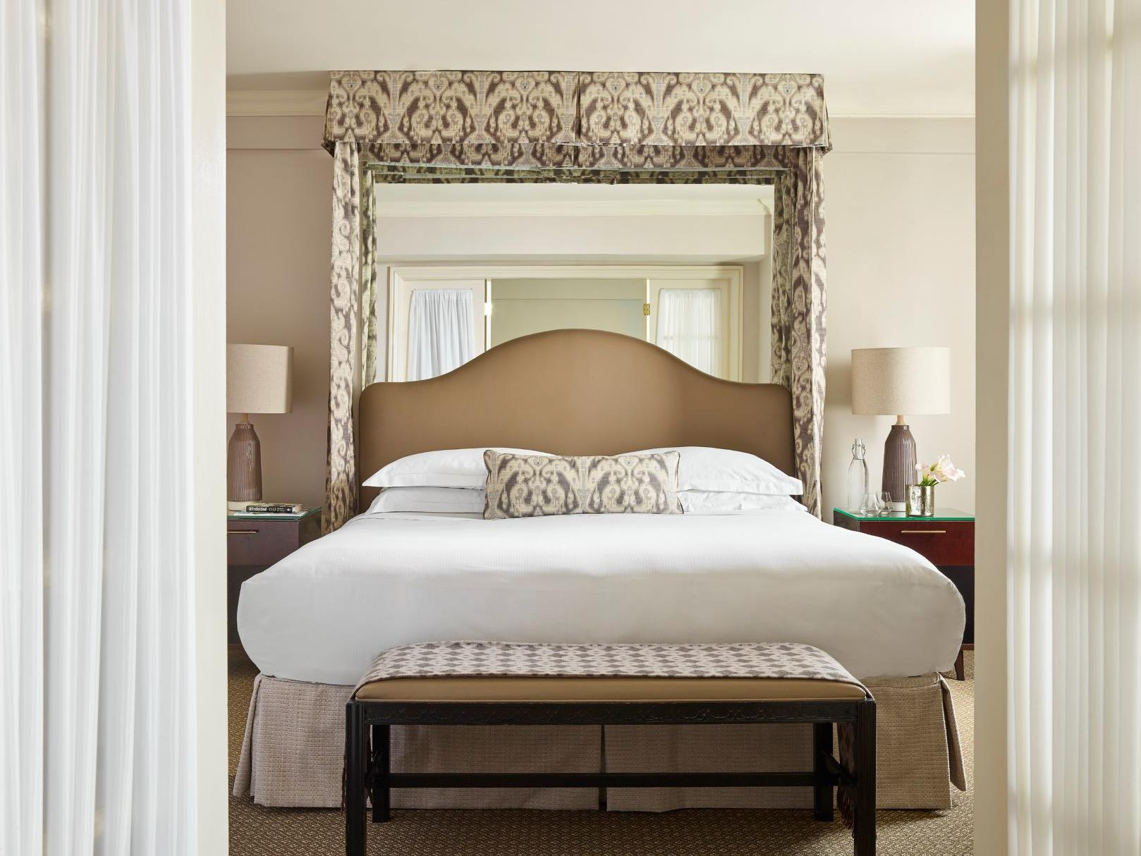 large bed with mirror on wall above and two side tables