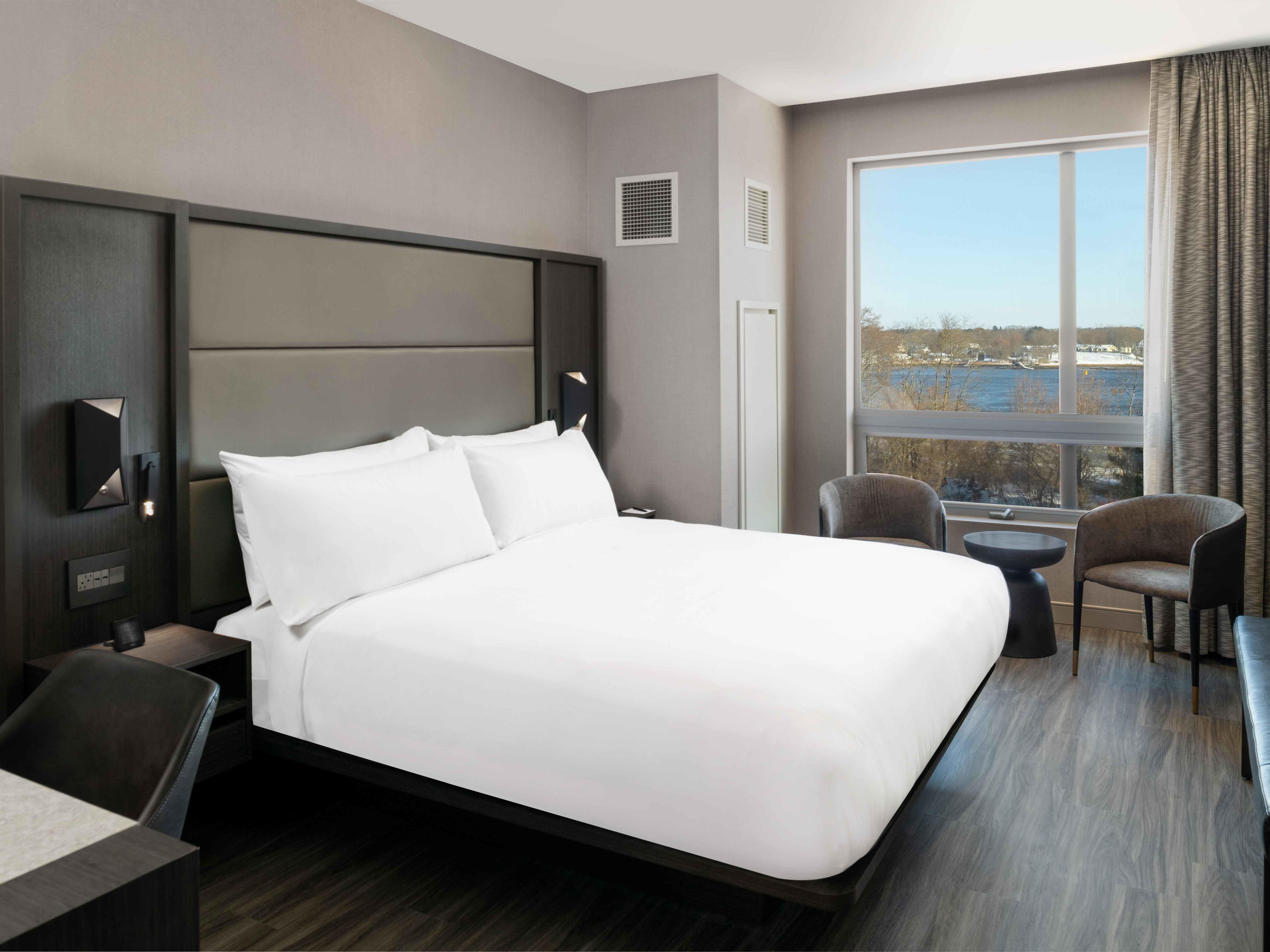 cozy bed in hotel room with water views