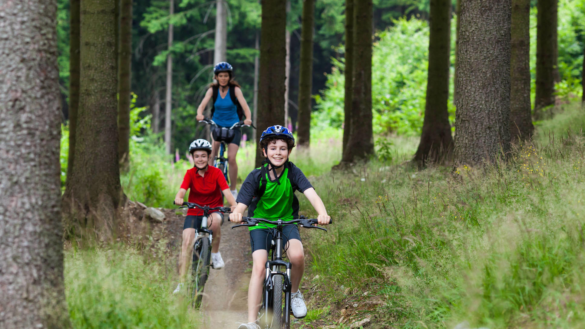 a woman and her children riding bikes in a forest