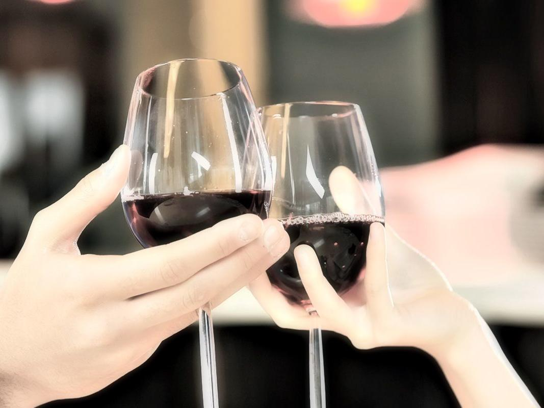 Couple clinking glasses of red wine