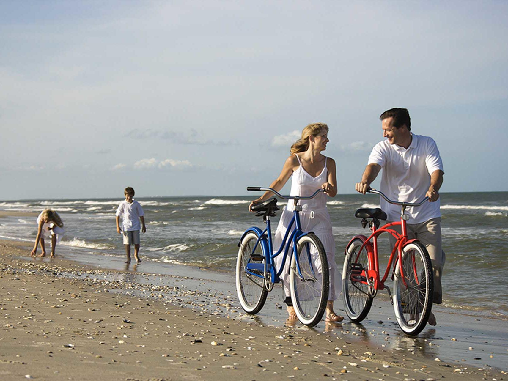 couple with bicycles on beach and kids walking behind