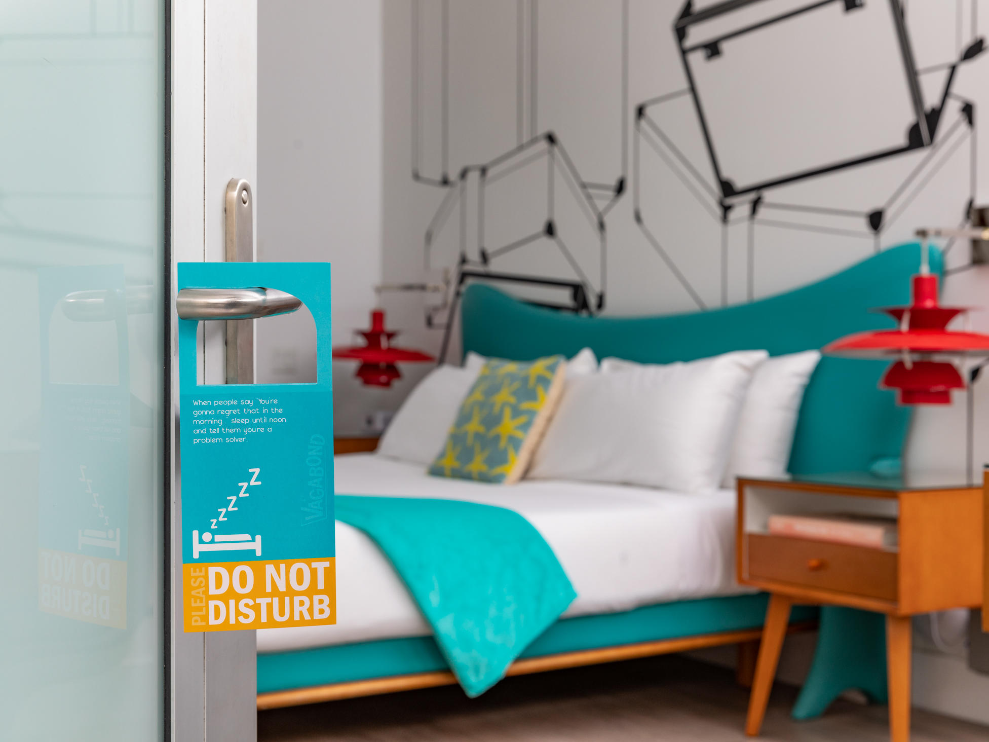 DO not disturb sign places on the door handle that is ajar with the King size bed in the background