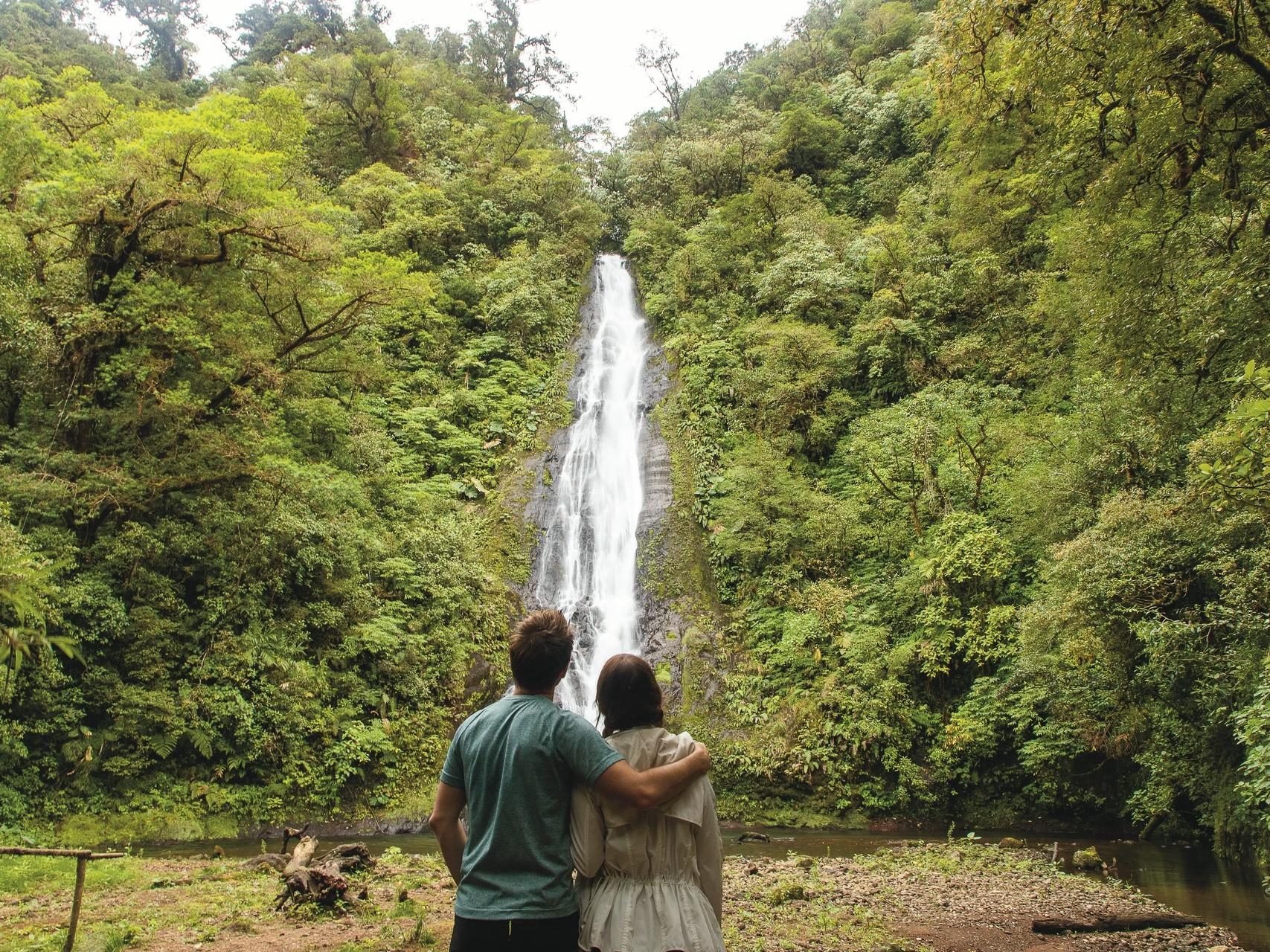 couple standing in front of watefall