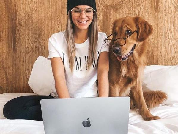 Woman on laptop in bed next to golden retriever with glasses