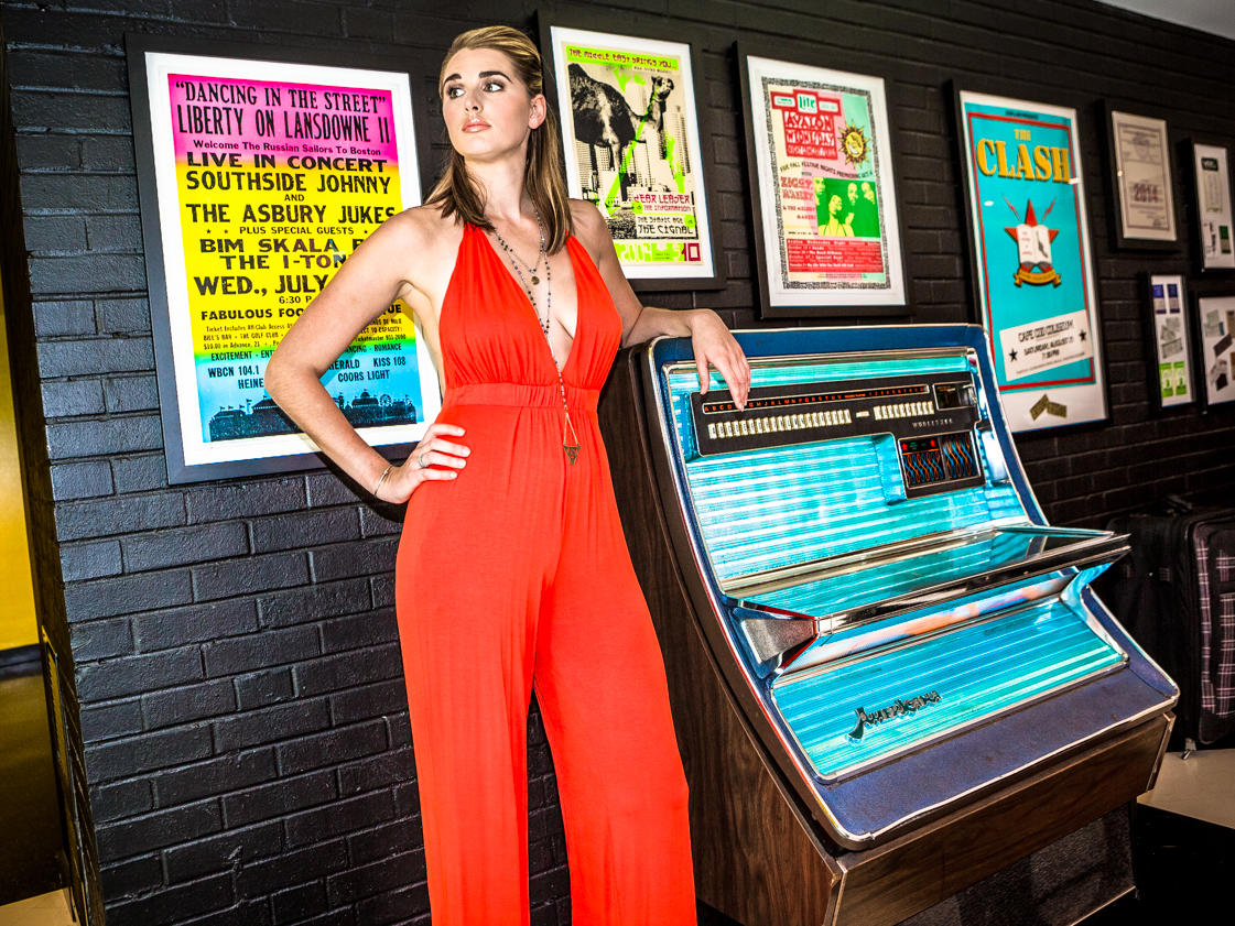 Woman in red jumpsuit leaning against jukebox