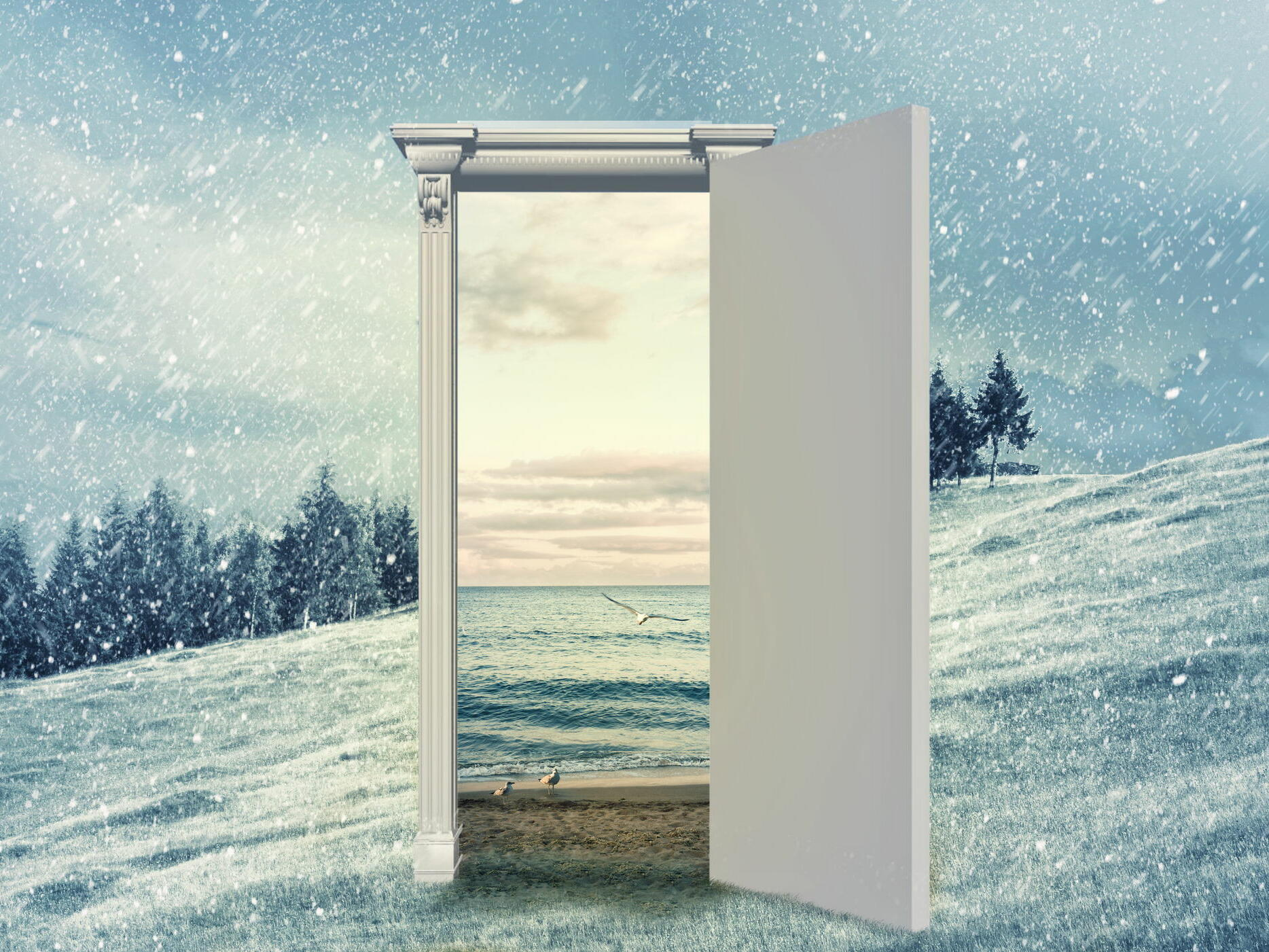 door in the middle of snowy mountain with view to beach