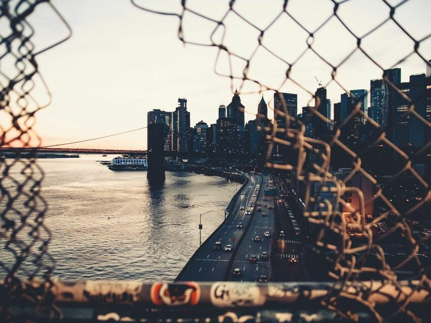 skyline view of NYC East river at sunset through a hole in the fence.