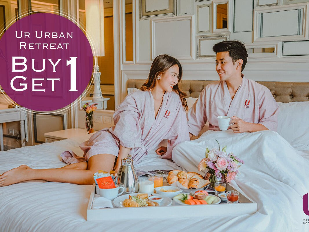 Couple having morning tea on bed at U Hotels and Resorts
