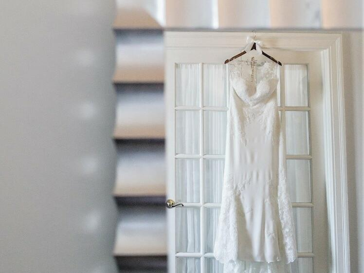 Wedding dress hanging from a door reflected in a silver mirror.