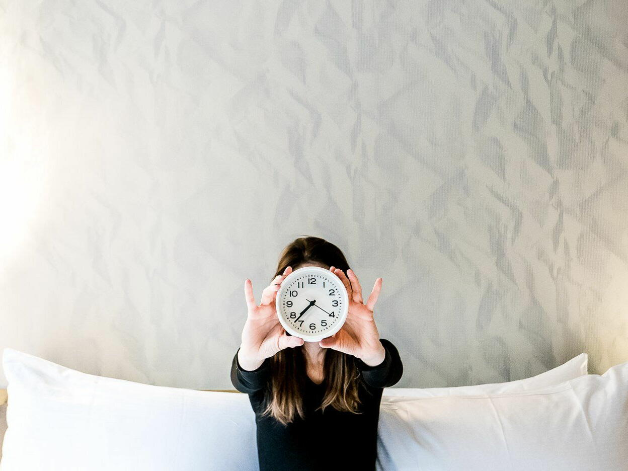 Girl holding a clock infront of her face at The Time New York