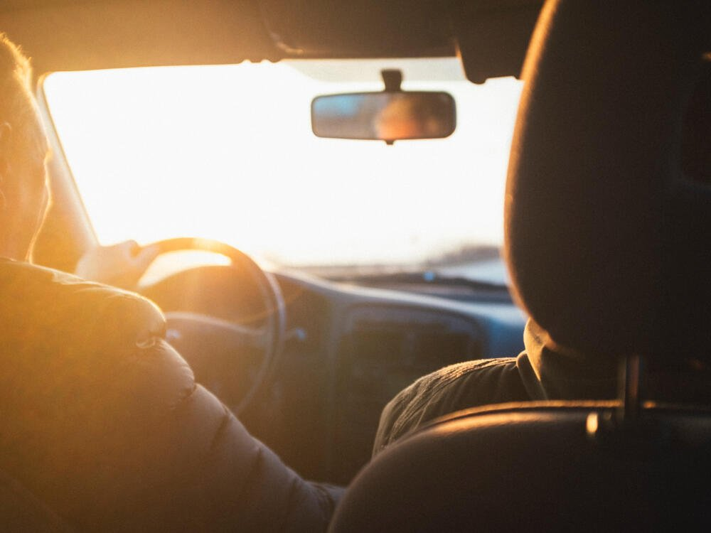 man happily driving his car with the sun in his eyes