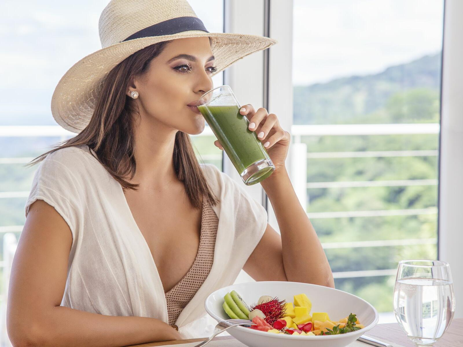 woman sipping juice at table