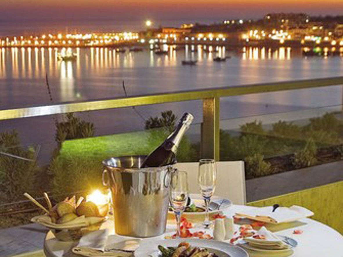 A table set for dinner with a sea view at Hotel Cascais Miragem