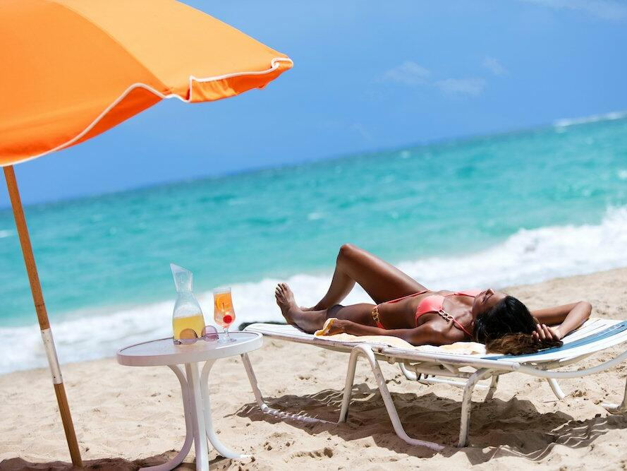 woman laying on lounge chair at the beach