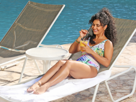 woman laying on lounge chair holding cocktail drink