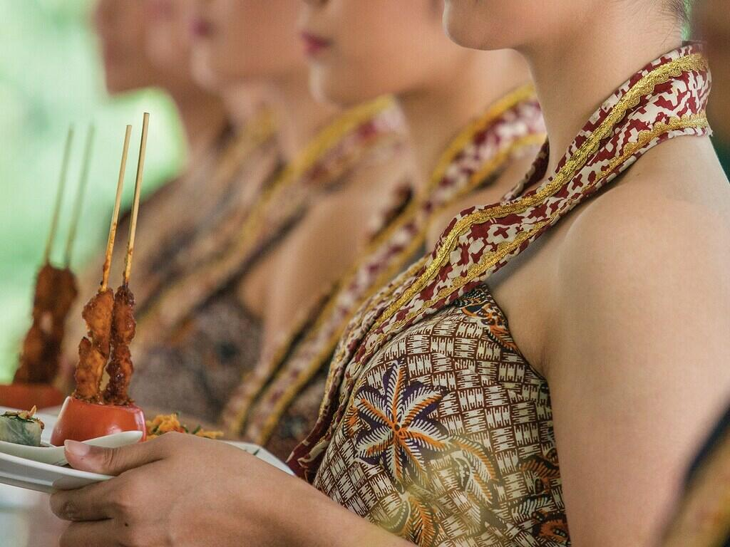 Ladies dressed in traditional clothes holding cooked meat dishes ready to serve