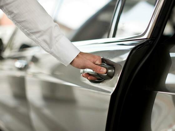 Close-up of hand holding car door handle at Dream Nashville