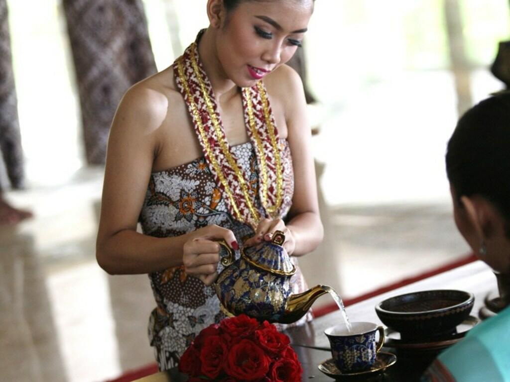 A lady dressed in traditional clothes pouring tea for a guest at Patehan Royal High Tea in Royal Ambarrukmo Yogyyakarta