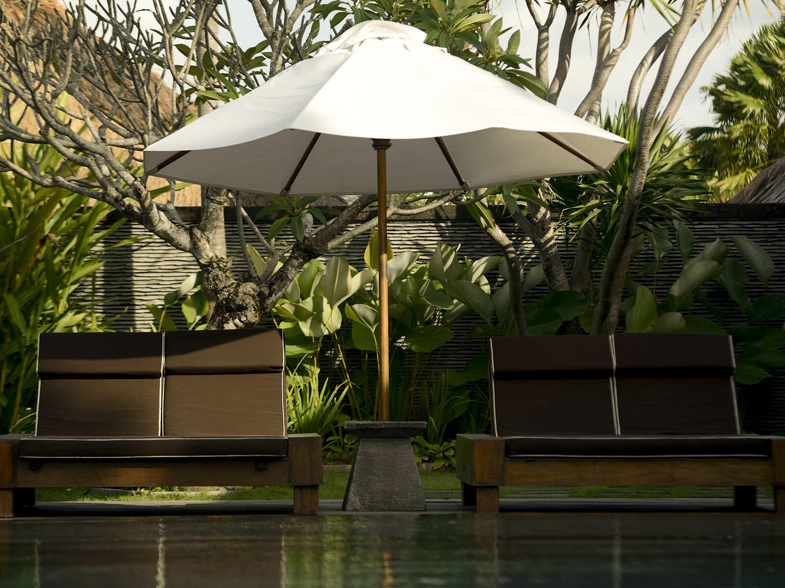 View of a hut with benches near the river at Peppers Seminyak