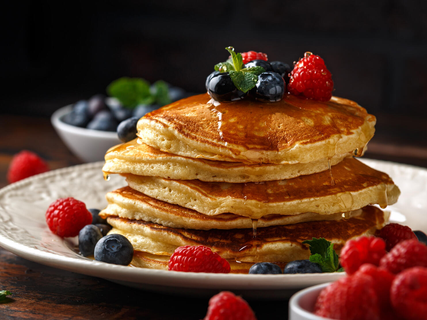 A stack of pancakes with berries and syrup served at Royal on the Park Hotel