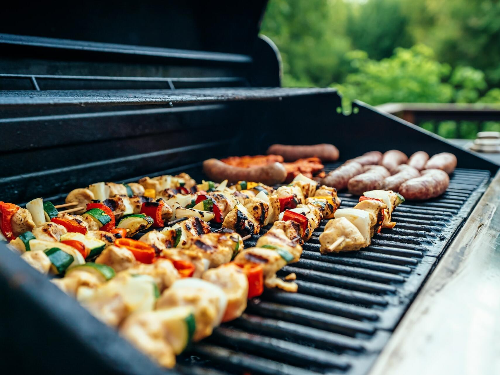 A barbeque grill with meat kebabs, vegetable kebabs and sausages