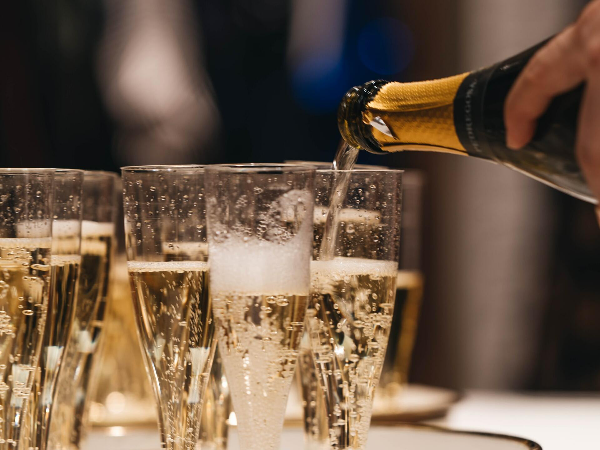 A man pouring Champagne into Champagne glasses at Pine Inn