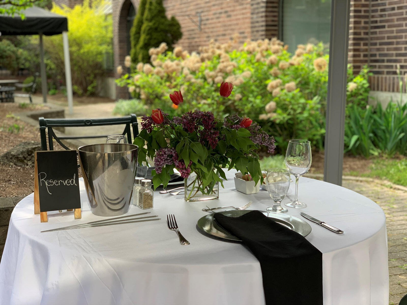 dining table in a garden with flowers at The Inn of Waterloo
