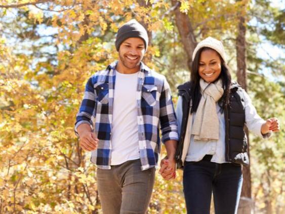couple-walking-through-fall-woodlands