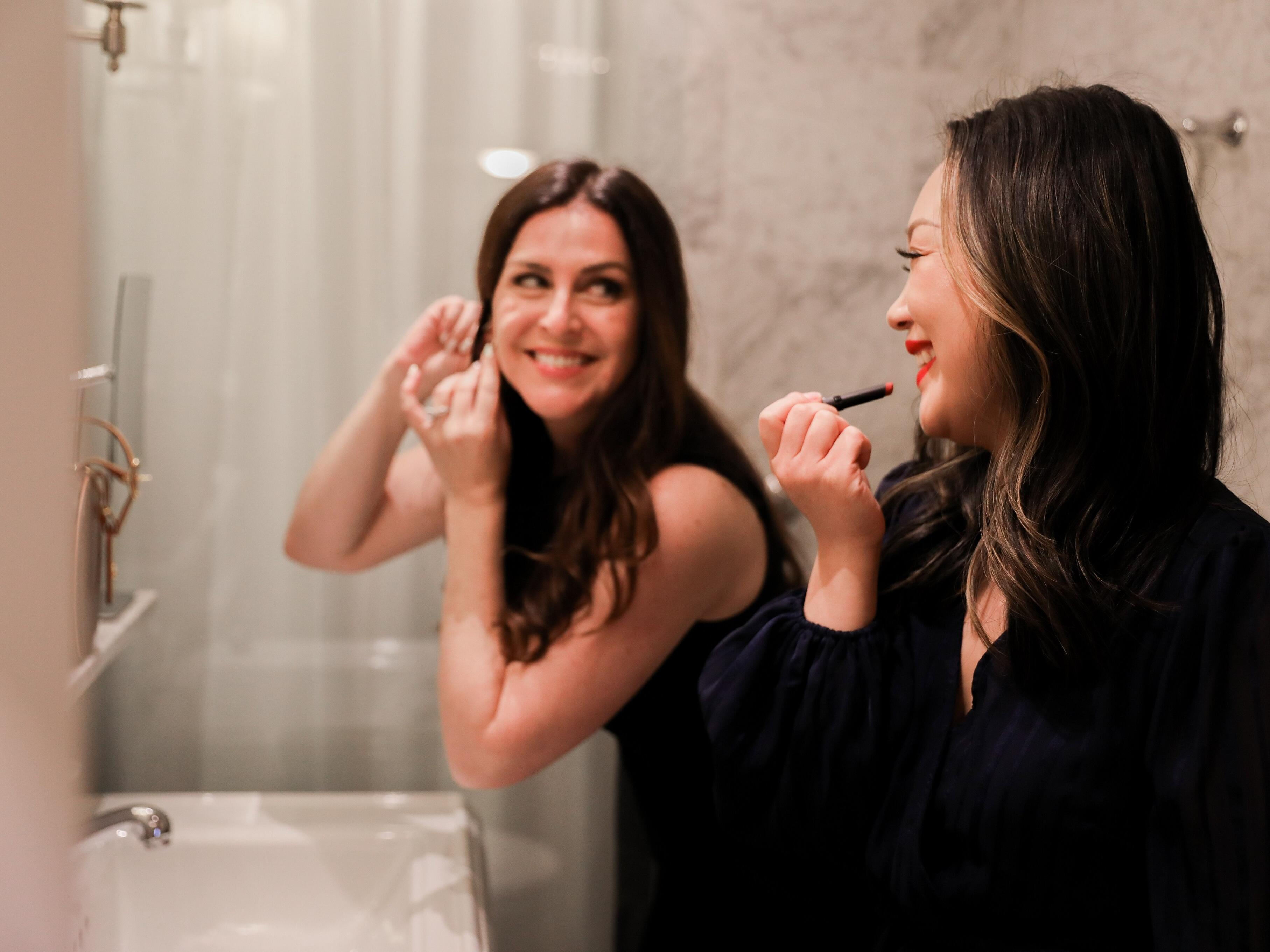 Two women in front of a mirror putting on makeup and earrings.