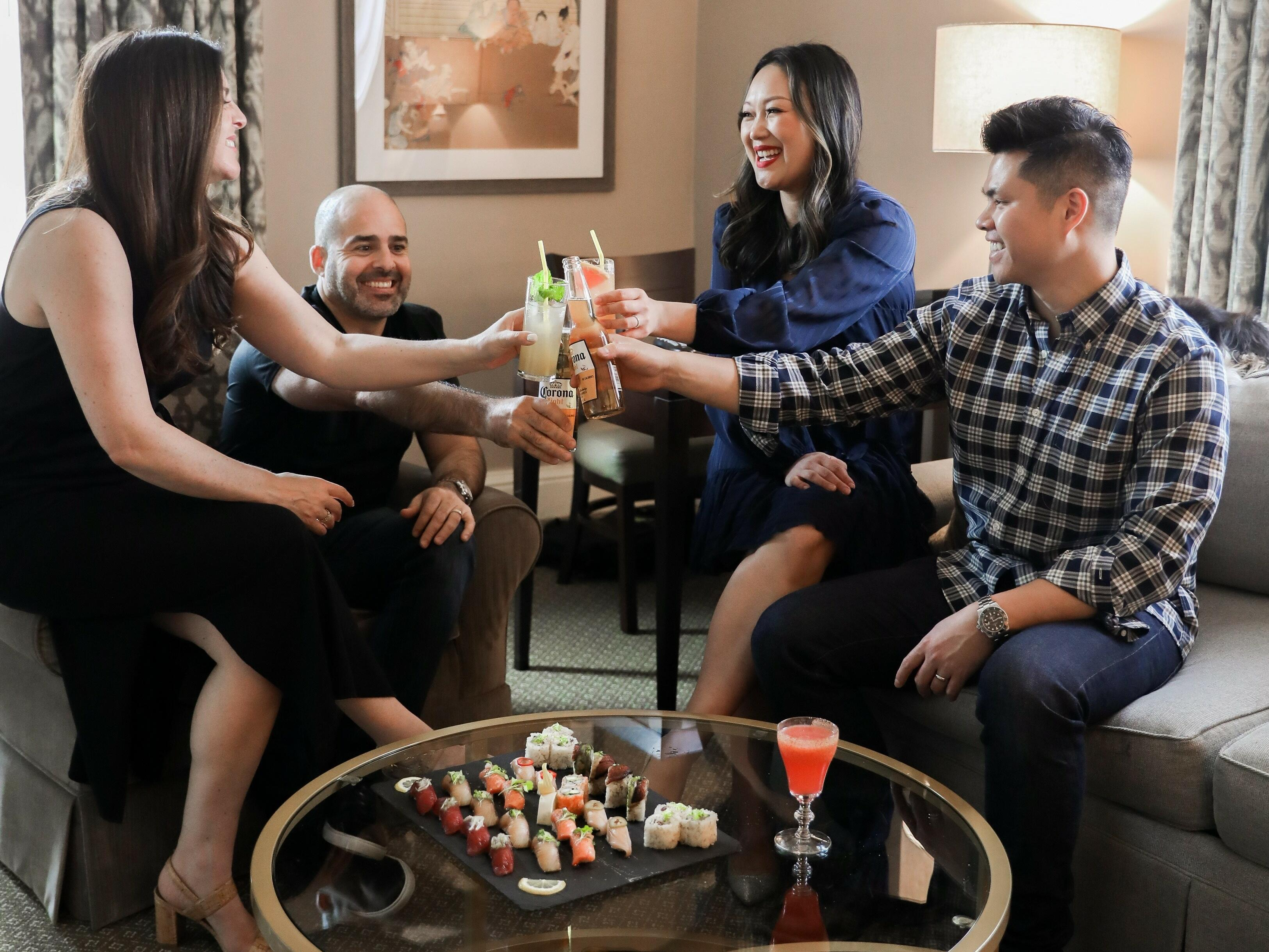 Four people in a living room with a sushi platter and cocktails.