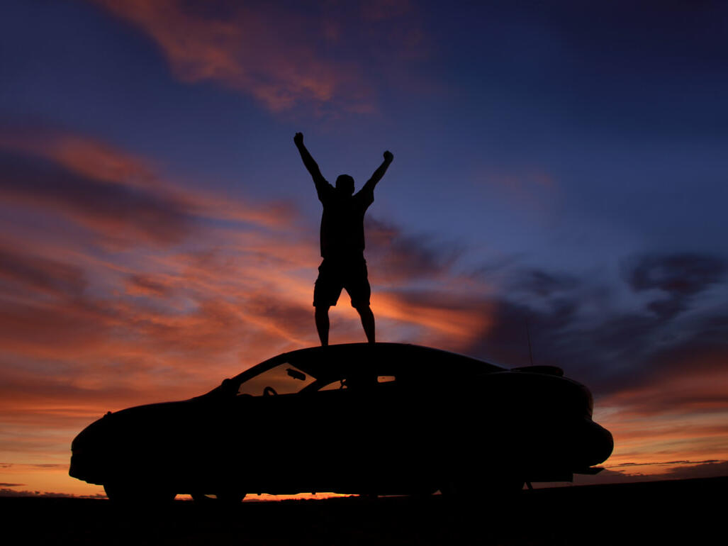 A man standing on a car watching the sunset