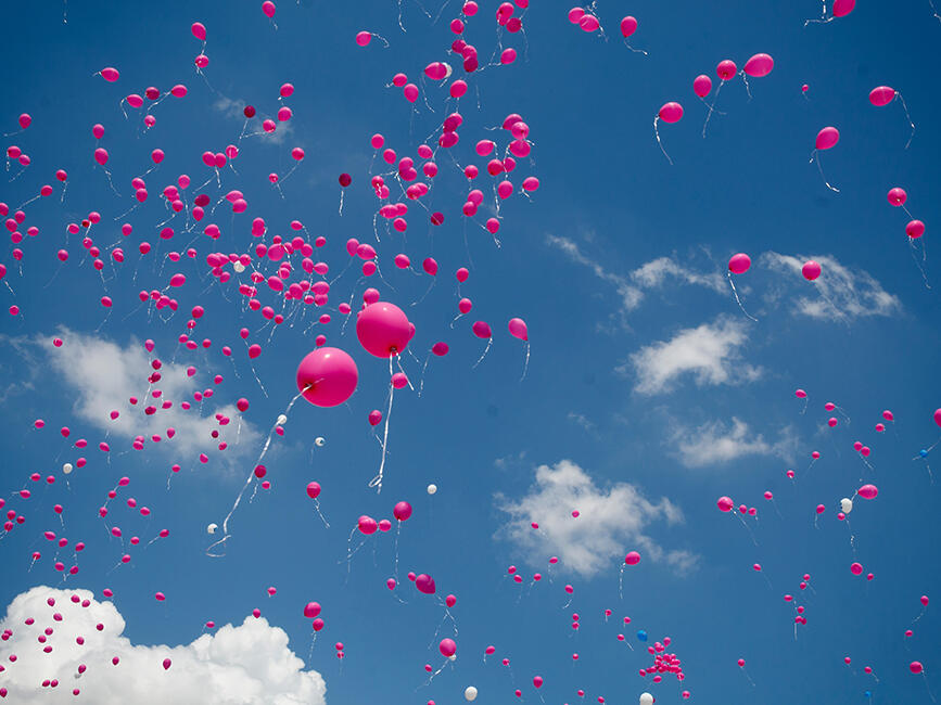 pink balloons floating into the sky