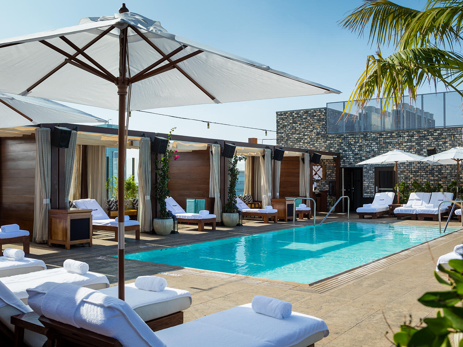 Pool setting at Dream Hollywood; view of pool and white reclining poolside chaises