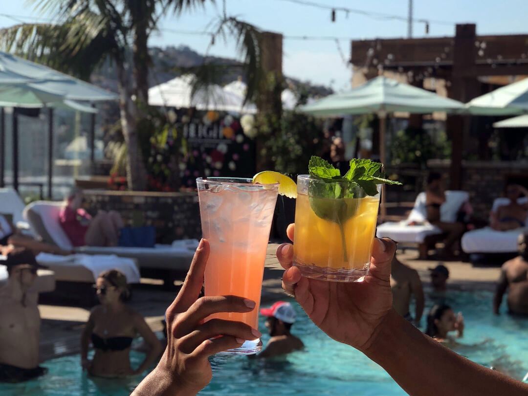 View of the pool in the background with two of our newest summer cocktails in the foreground