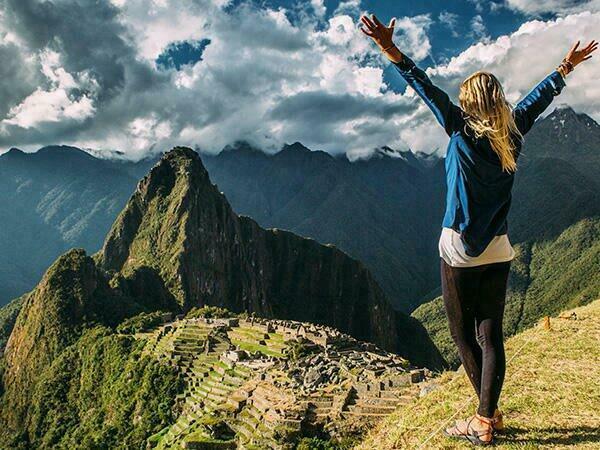 A tourist at the top of Machu Picchu Mountains near Sumaq Hotel