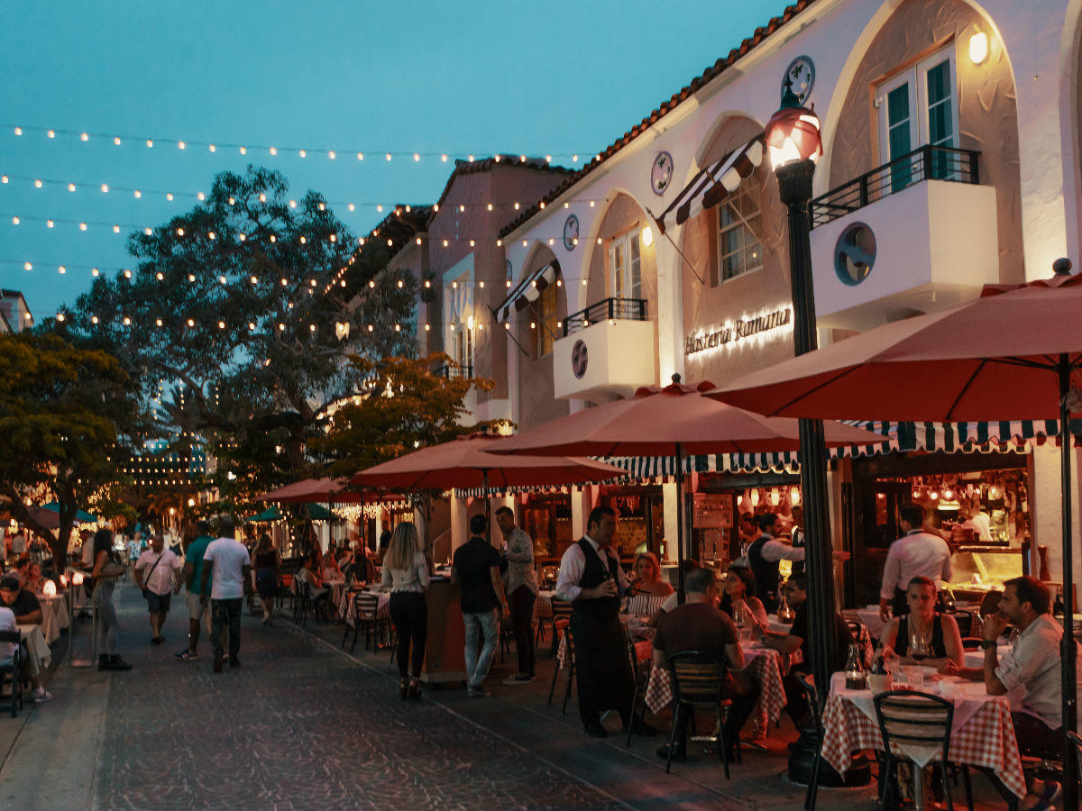 people dining and walking through row of outdoor dining tables and restaurants