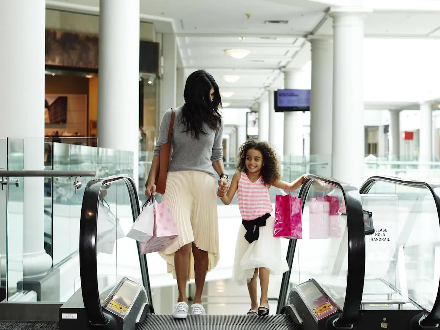 Mother and daughter holding shopping bags on escalator