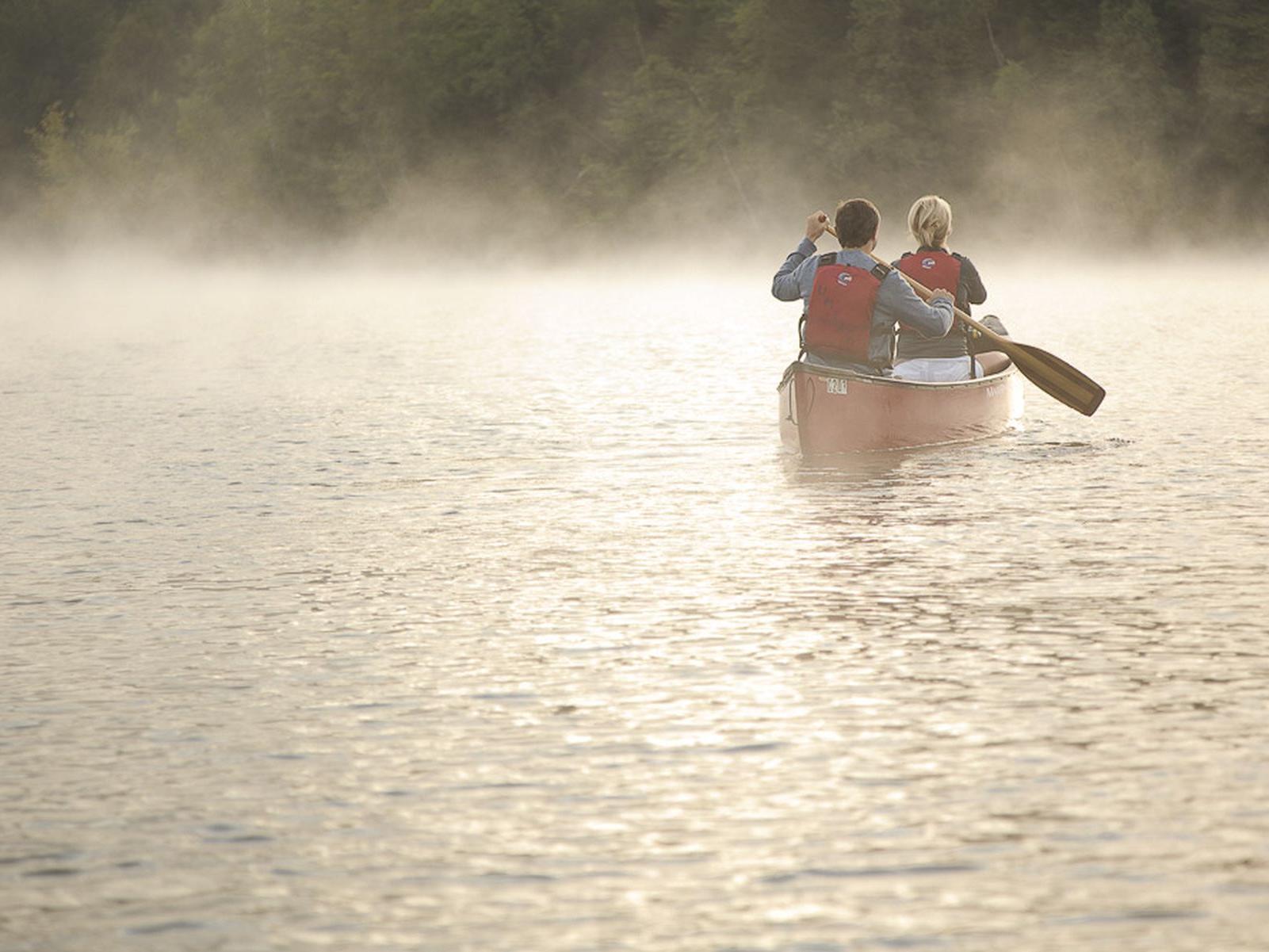 Couple canoeing on a misty lake.