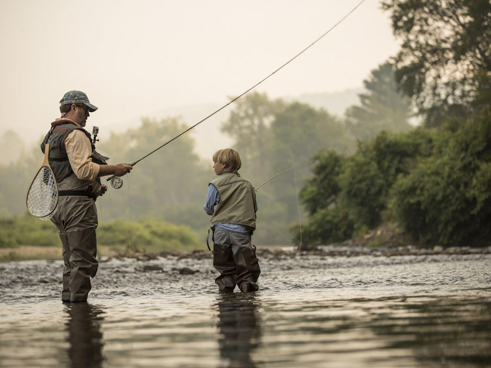 Father and son fly-fishing at sunrise.