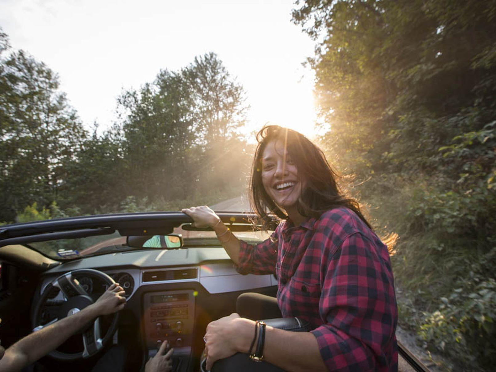 Girl in a Jeep looking back and laughing.