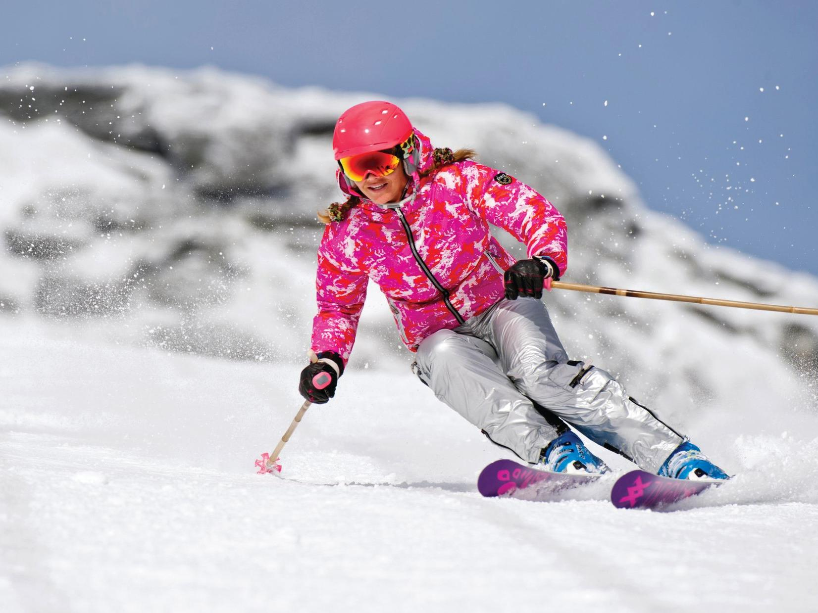 Skier in pink attire making a tight turn.