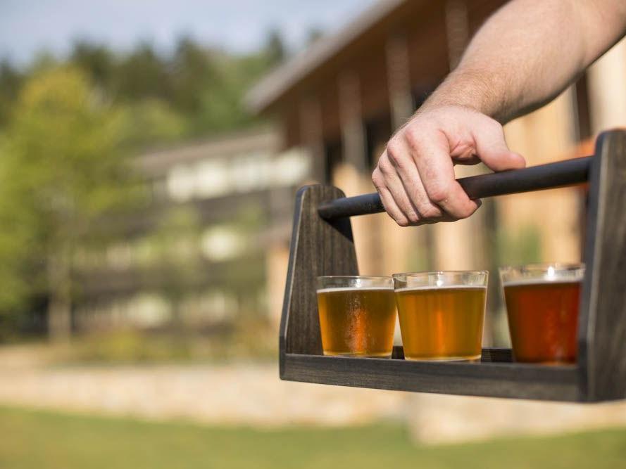 A hand holding a flight of craft brews.