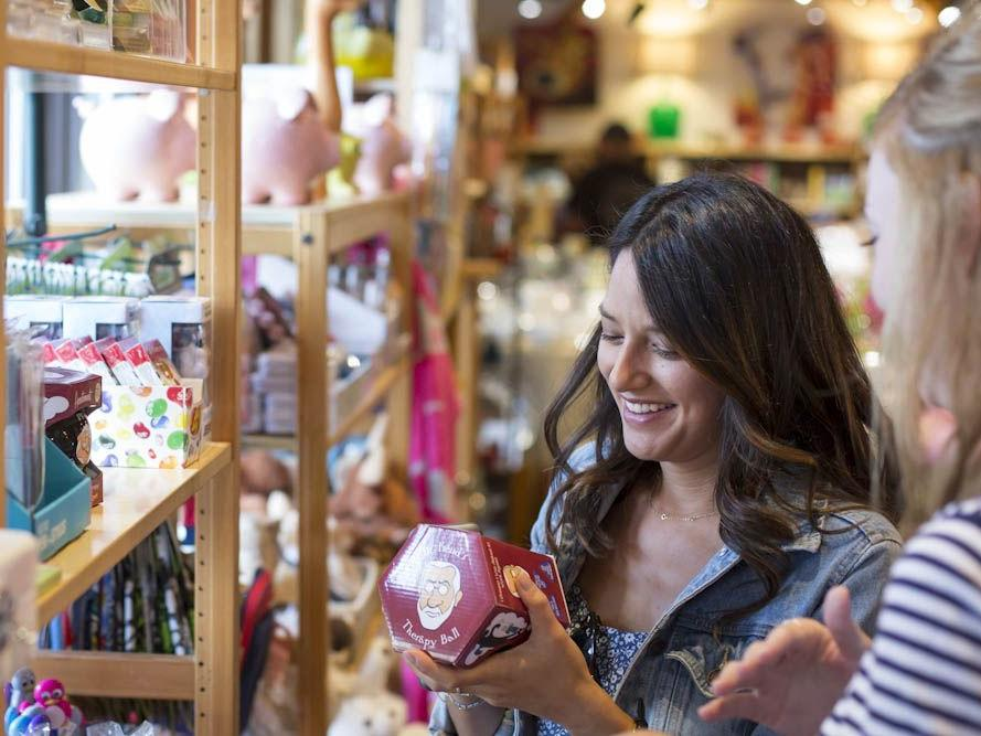 Two girls shopping. One is holding a Dr. Freud's Therapy Ball.
