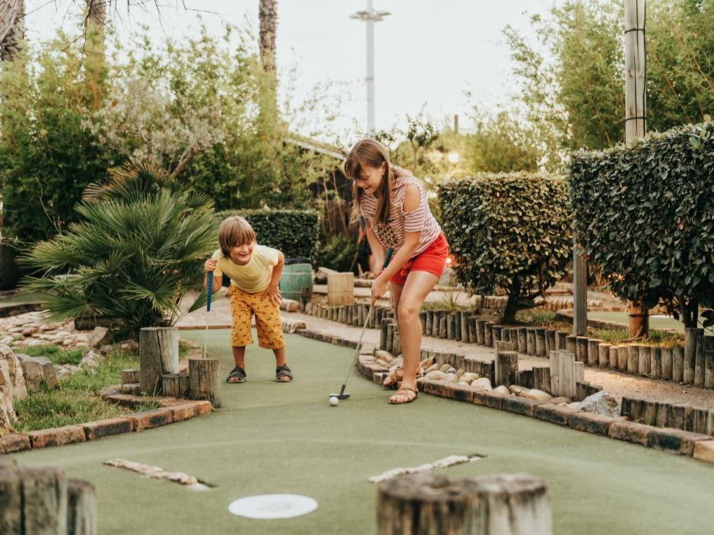 two children playing putt putt golf