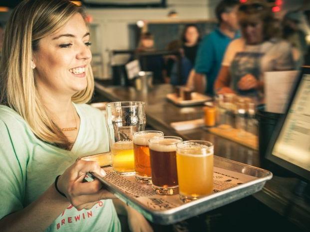 woman holding beer flight